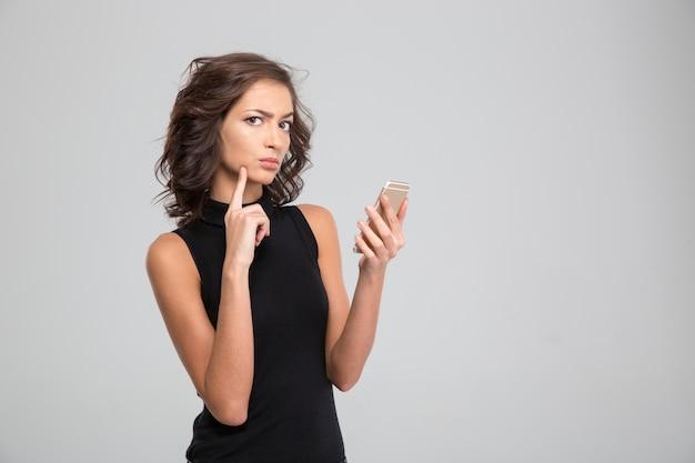 Geërgerde jonge krullende vrouw in zwarte top met behulp van mobiele telefoon