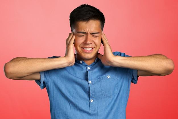 Geërgerde jonge mens die oren met handen stopt