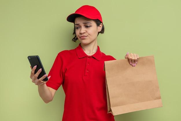 Geërgerde jonge mooie bezorger die papieren voedselverpakkingen vasthoudt en naar de telefoon kijkt