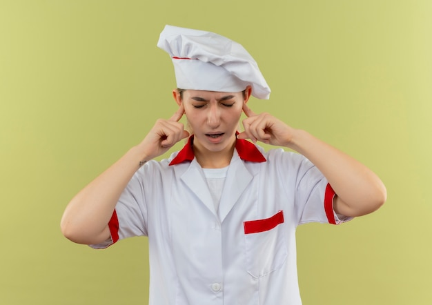 Geërgerde jonge mooie kok in uniform van de chef-kok die vingers in de oren steekt met gesloten ogen geïsoleerd op een groene muur