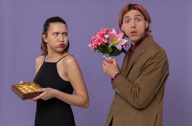 Geërgerde jonge vrouw die een chocoladedoos vasthoudt en kijkt naar een angstige jonge man die een boeket bloemen vasthoudt