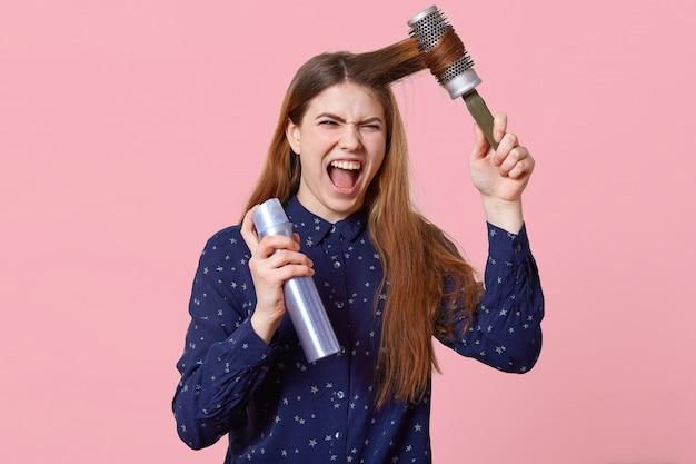 Geërgerde jonge vrouw kamt haar haar, ontevreden met shampoo, houdt haarborstel en haarlak vast, kijkt geïrriteerd naar de camera