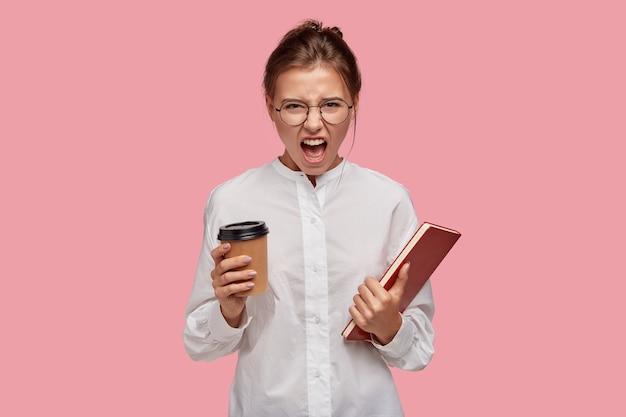 Geërgerde jonge vrouw met bril poseren tegen de roze muur