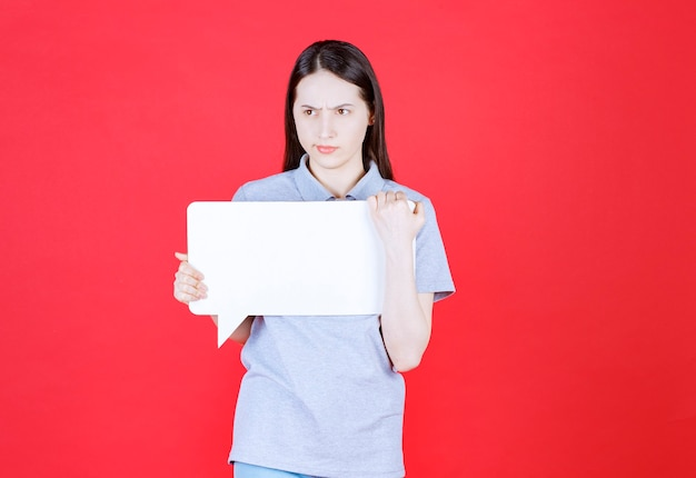 Geërgerde jonge vrouw met wit bord holding