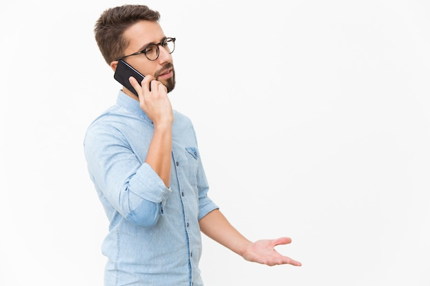 Geërgerde kerel die op mobiele telefoon spreekt