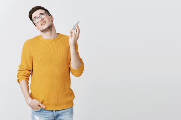 Geërgerde man die het gesprek wil beëindigen, zijn ogen wil rollen en zijn mobiele telefoon wil wegtrekken