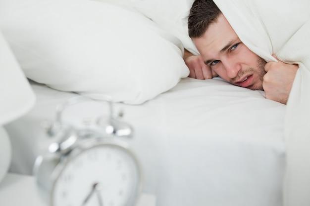 Geërgerde man die zijn oren behandelt terwijl zijn wekker rinkelt