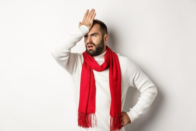 Geërgerde man klapt op zijn voorhoofd en vloekt, vergeet kerstcadeaus te kopen, facepalm en staande tegen een witte achtergrond