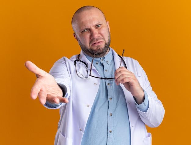 Geërgerde mannelijke arts van middelbare leeftijd met een medisch gewaad en een stethoscoop die een bril vasthoudt die de hand naar voren uitstrekt en naar de voorkant kijkt geïsoleerd op een oranje muur