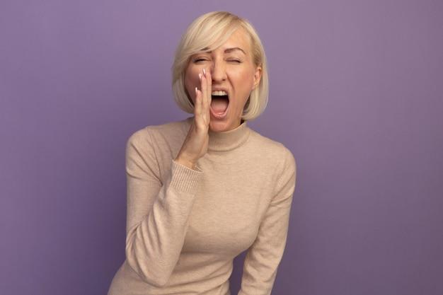 Geërgerde mooie blonde slavische vrouw houdt de hand dicht bij de mond en schreeuwt tegen iemand die op een paarse muur is geïsoleerd