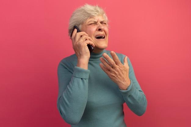 Geërgerde oude vrouw met blauwe coltrui die aan de telefoon praat en hand in de lucht houdt met gesloten ogen geïsoleerd op roze muur met kopieerruimte