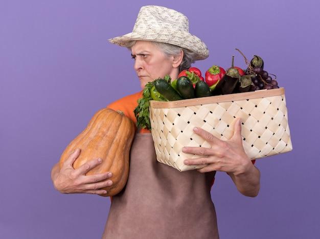 Geërgerde oudere vrouwelijke tuinman met een tuinhoed met een groentemand en een pompoen die naar de zijkant kijkt die op een paarse muur met kopieerruimte wordt geïsoleerd
