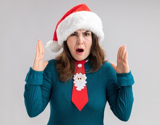 Geërgerde volwassen blanke vrouw met kerstmuts en kerststropdas houdt de handen open en doet alsof ze iets vasthoudt dat op een witte muur is geïsoleerd met kopieerruimte