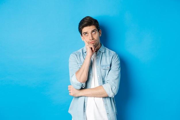Geërgerde volwassen man die met zijn ogen rolt en er verveeld uitziet, onverschillig staat tegen een blauwe achtergrond in een casual outfit