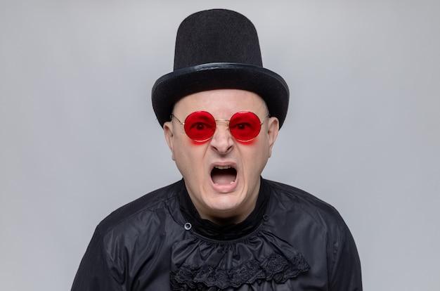 Geërgerde volwassen man met hoge hoed en met zonnebril in zwart gotisch overhemd schreeuwend tegen iemand die kijkt