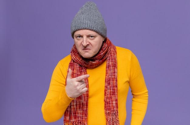 Geërgerde volwassen man met wintermuts en sjaal om zijn nek wijzend naar de zijkant