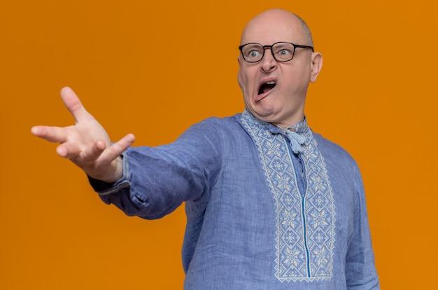 Geërgerde volwassen slavische man in blauw shirt en met optische bril die met zijn hand naar de zijkant kijkt en wijst