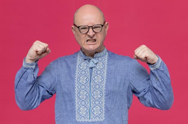 Geërgerde volwassen slavische man in blauw shirt met een bril die vuisten houdt