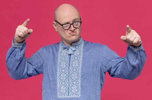 Geërgerde volwassen slavische man in blauw shirt met een optische bril die naar voren wijst