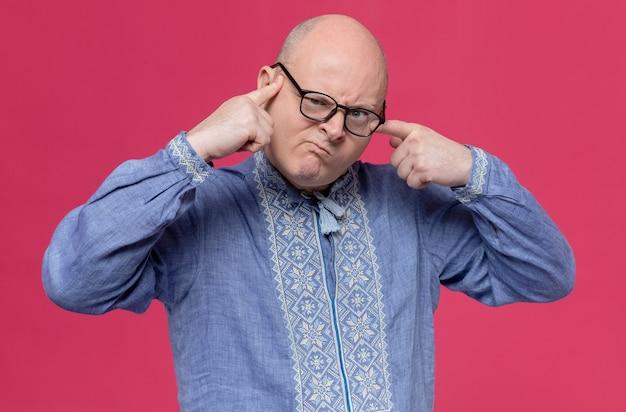 Geërgerde volwassen slavische man in blauw shirt met een optische bril die vingers op zijn gezicht legt