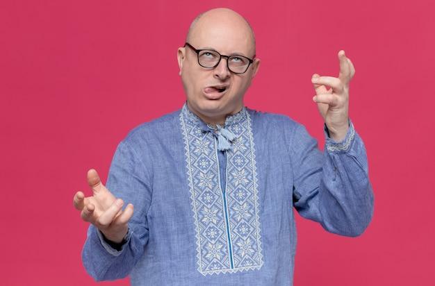 Geërgerde volwassen slavische man in blauw shirt met optische bril die handen open houdt en omhoog kijkt