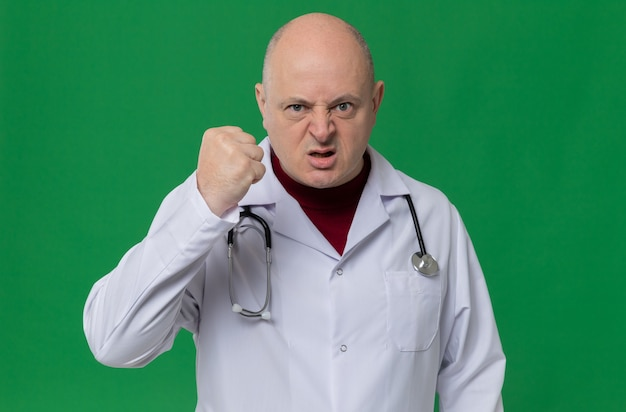 Geërgerde volwassen slavische man in doktersuniform met een stethoscoop die zijn vuist balt