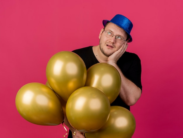 Geërgerde volwassen slavische man met een optische bril met een blauwe feesthoed legt de hand op het oor en houdt heliumballonnen vast die naar de zijkant kijken