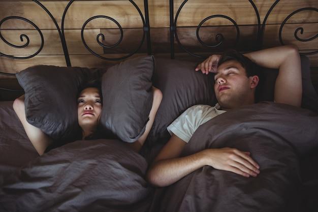 Geërgerde vrouw die haar oren bedekt met kussens om het snurken in de slaapkamer te blokkeren