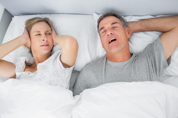 Geërgerde vrouw die haar oren blokkeert tegen lawaai van echtgenoot die snurkt
