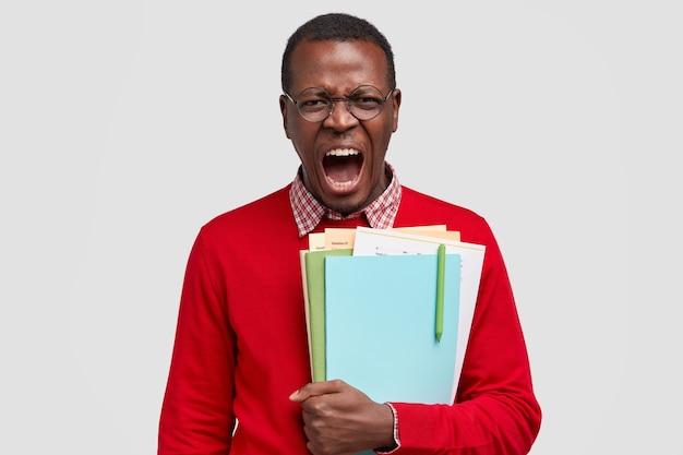 Geërgerde wanhopige student schreeuwt boos, heeft een ontevreden gelaatsuitdrukking, schreeuwt dat hij het studeren beu is, draagt blocnote, boeken