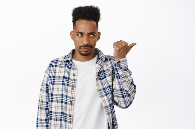 Geërgerde zwarte man wijst en kijkt recht naar logobanner, frons wenkbrauwen en staart boos op verkoopadvertentie, staande in vrijetijdskleding op wit
