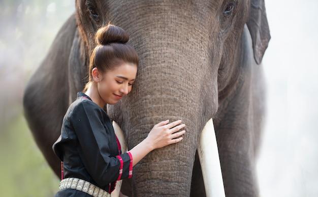Geest van azië, het platteland van thailand; boer en olifant op de achtergrond van zonsopgang. aziatische cultuur