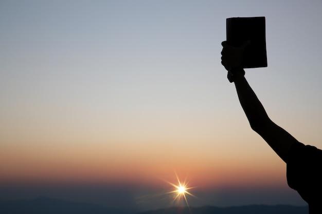 Geestelijke gebedshanden die de bijbel vasthouden