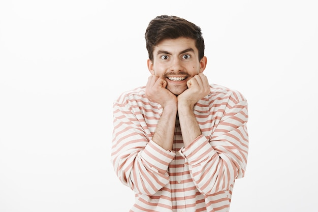 Gefascineerd geïnteresseerd aantrekkelijke volwassen man met snor, hoofd op handen leunend en nieuwsgierig starend, luisterend interessant verhaal, opgewonden over grijze muur