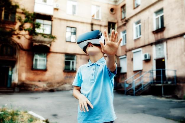 Gefascineerd jongetje met vr virtual reality-bril. buitenshuis
