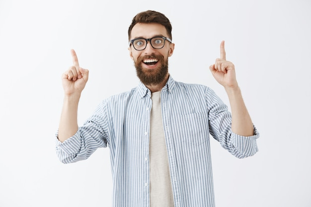 Gefascineerde en opgewonden bebaarde man die tegen de witte muur poseert