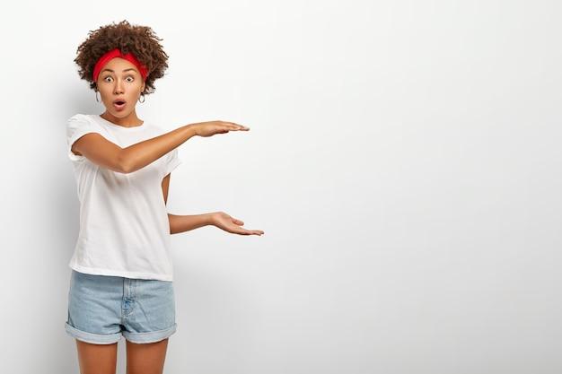 Gefascineerde etnische vrouw legt de grootte van een object uit, bespreekt iets groots of groots, introduceert een enorm object met verbazing, houdt de mond open, gekleed in een vrijetijdskleding, geïsoleerd op een witte muur