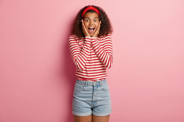 Gefascineerde gelukkige tiener met krullend haar poseren in gestreepte rode trui