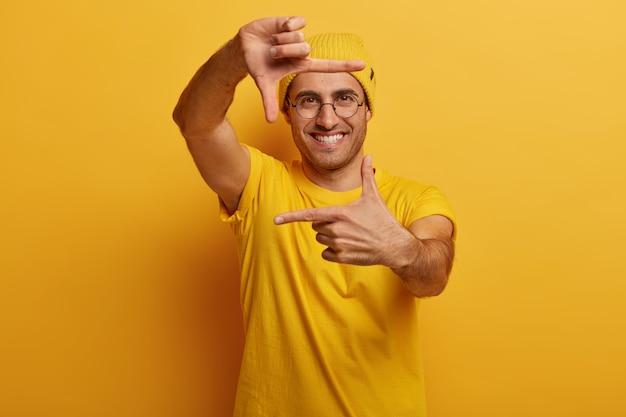 Gefascineerde jongeman met vrolijke uitdrukking, maakt handframe, probeert het juiste perspectief te vinden, doet alsof hij een scène fotografeert
