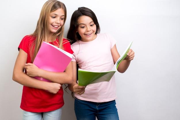 Gefascineerde multi-etnische schoolmeisjes die werkboeken lezen