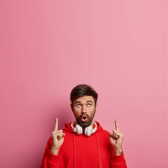 Gefascineerde onder de indruk bebaarde man meloman wijst naar boven, toont iets verbazingwekkends naar boven, gebruikt stereokoptelefoon om naar muziek te luisteren, hijgt van verwondering, geïsoleerd op roze muur. promo concept
