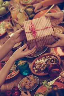 Gefeliciteerd! bovenaanzicht van een groep mensen die samen dineren terwijl mannelijke handen een geschenkdoos geven aan sommige vrouwen