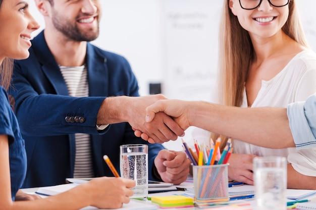 Gefeliciteerd! close-up van zakenmensen in slimme vrijetijdskleding die handen schudden en glimlachen terwijl ze samen aan tafel zitten