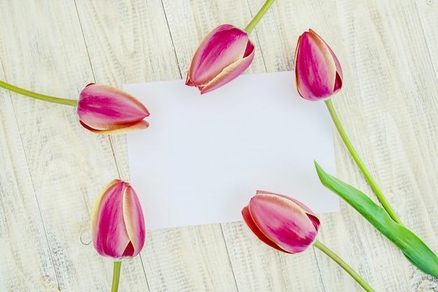 Gefeliciteerd en tulpen op een lichte achtergrond. selectieve aandacht.