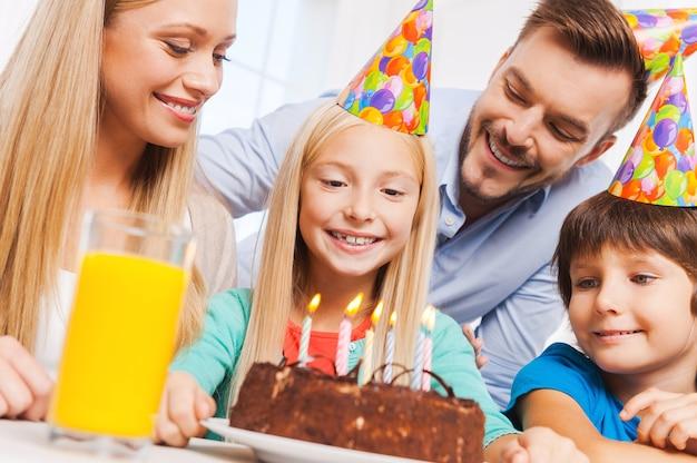 Gefeliciteerd! gelukkig gezin van vier vieren de verjaardag van een gelukkig klein meisje dat aan tafel zit met een verjaardagstaart erop