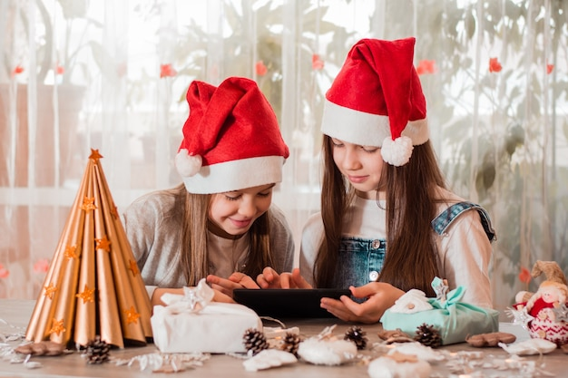 Gefeliciteerd in quarantaine. meisjes in kerstversiering communiceren met hun families via een tablet.