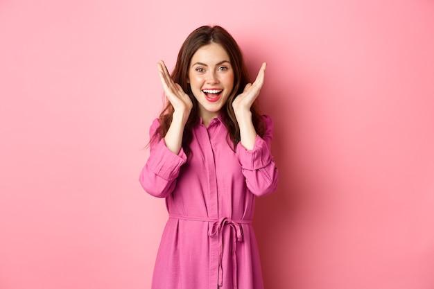 Gefeliciteerd met je verjaardag, open ogen en kijk verbaasd, ontvang geschenk, lachend opgewonden, staand tegen roze muur.