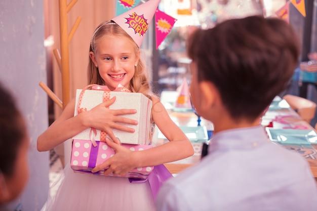 Gefeliciteerd met je verjaardag. positief feestvarken dat onder de indruk is van de cadeautjes en lacht naar haar vrienden