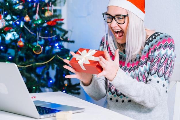 Gefeliciteerd met kerstmis online. glimlachend meisje thuis met behulp van laptop