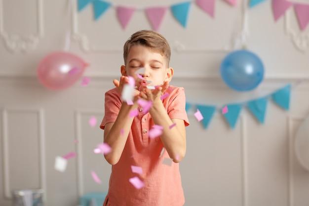 Gefeliciteerd portret van een gelukkige schattige jongen van 8-9 jaar oud in een feestelijk decor met confetti en geschenken.